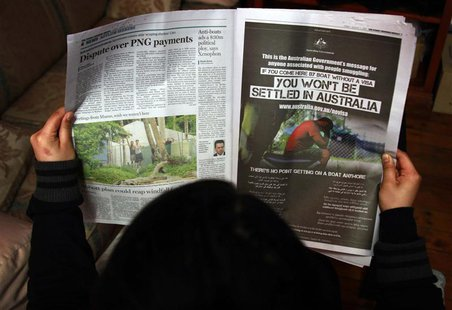 A woman reads a newspaper containing an advertisement (R) publicising the Australian government's new policy on asylum seekers arriving by b