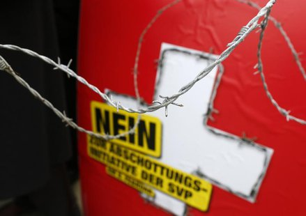 A poster against the 'mass immigration initiative' of the Swiss Socalist Party SPS is seen through barbed wire fence on the Federal Square b
