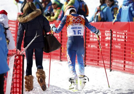 Bode Miller of the U.S. (R) leave the venue with his wife Morgan Beck after the men's alpine skiing giant slalom event at the 2014 Sochi Win