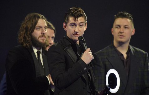 Alex Turner (C) of the Arctic Monkeys talks after being presented with the British Album award at the BRIT Awards, celebrating British pop m