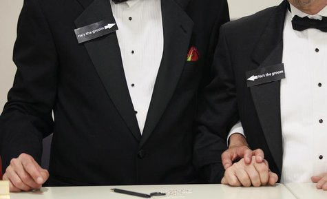 "Two men, both wearing signs that read ""he's the groom"", hold hands shortly after midnight after getting a civil union when Colorado's civil"