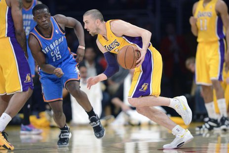 Feb 13, 2014; Los Angeles, CA, USA; Los Angeles Lakers guard Steve Blake (5) handles the ball defended by Oklahoma City Thunder guard Reggie
