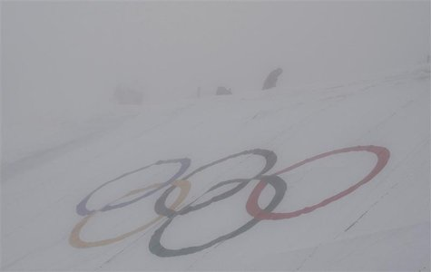 A man walks behind the Olympic rings ahead of the men's snowboard cross qualification round at the 2014 Sochi Winter Olympic Games in Rosa K