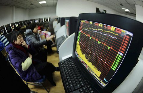 Investors look at computer screens displaying stock information at a brokerage house in Qingdao, Shandong province February 10, 2014. REUTER