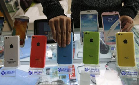 A clerk arranges Apple's iPhone 5C phones on racks bearing the logo of China Mobile, at a mobile phone shop in Beijing December 23, 2013. RE
