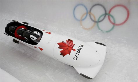 Canada's pilot Justin Kripps (front) and his teammates speed down the track during a four-man bobsleigh training session at the Sanki Slidin