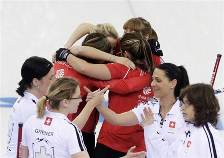 Britain's curling team celebrates with a group hug after winning in their women's bronze medal curling game against Switzerland (foreground)