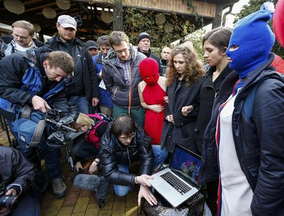 Russian punk band Pussy Riot members Maria Alyokhina (3rd R) and Nadezhda Tolokonnikova (2nd R) along with masked members show a video to jo