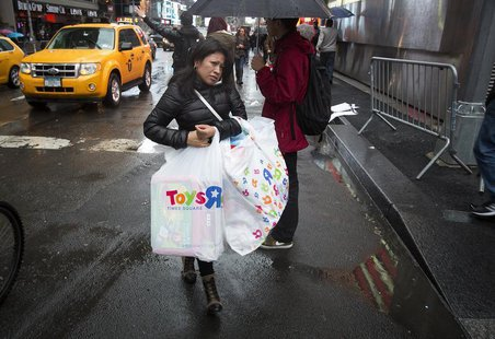 A woman carries bags of purchases though Times Square in New York, December 23, 2013. REUTERS/Carlo Allegri