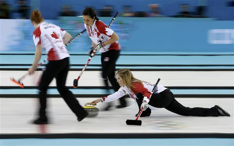Canada's lead Dawn McEwen (L) and second Jill Officer prepare to sweep as skip Jennifer Jones (R) delivers a stone in their women's gold med