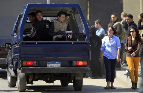 Foreign journalists and relatives of Al-Jazeera journalists walk near a police vehicle outside Cairo's Tora prison, where the trial of Al Ja