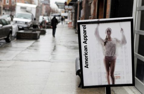 Pedestrians walk past an American Apparel sign outside one of their stores in New York April 1, 2011. REUTERS/Lucas Jackson