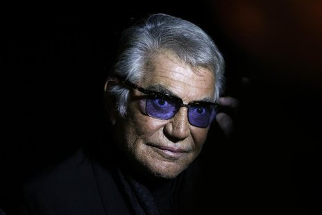 Italian designer Roberto Cavalli poses before the start of his Spring/Summer 2014 collection during Milan Fashion Week September 21, 2013. R