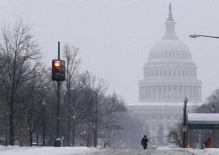 A pedestrian walks up the middle of North Capitol Street towards the U.S. Capitol building, on largely deserted streets, as a major snow sto