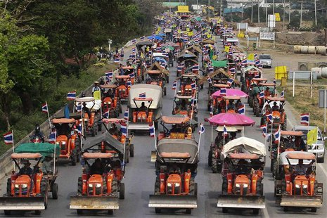Farmers drive their tractors and other farming vehicles on a road in Ang Thong province, towards Bangkok, February 20, 2014. REUTERS/Stringe