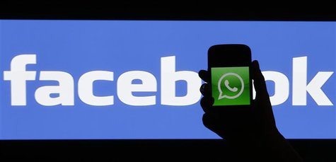 A woman holds a smartphone displaying WhatApps' logo in front of the screen with the Facebook logo in this photo illustration taken in Pragu