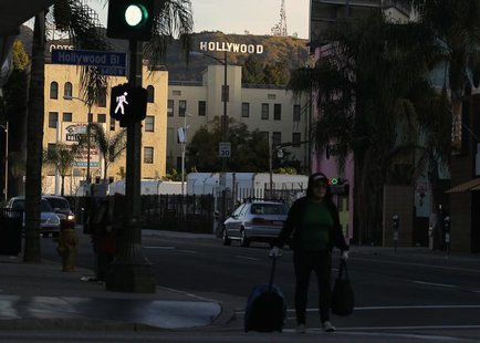 A women walks with her belongings under the Hollywood sign and across Hollywood Boulevard in Hollywood, California February 22, 2012. REUTER