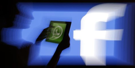 A woman holds a tablet displaying WhatsApp's logo in front of the screen with the Facebook logo in this photo illustration taken in Prague F
