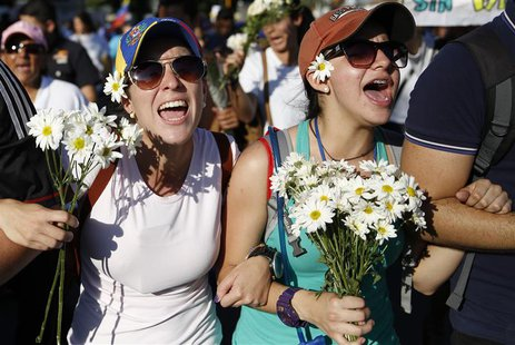 Supporters of opposition leader Leopoldo Lopez hold flowers and shout during a rally to promote peace in Caracas February 20, 2014. REUTERS/