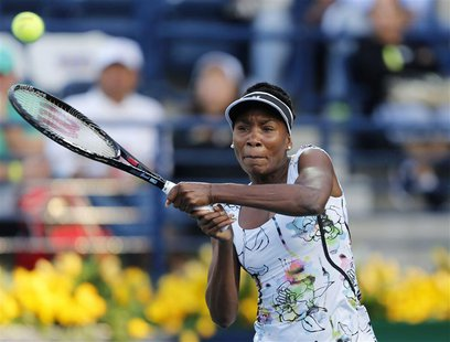 Venus Williams of the U.S. returns the ball to Caroline Wozniacki of Denmark during their women's singles semi-final match at the WTA Dubai