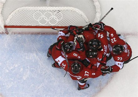 Canada's players congratulate goalie Carey Price after Canada defeated Team USA in their men's ice hockey semi-final game at the Sochi 2014