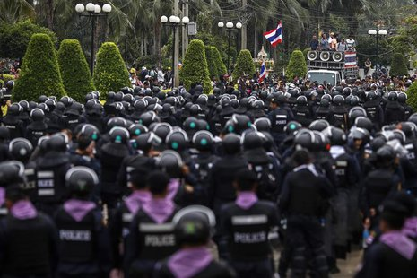 Thai riot police stand guard as anti-government protesters rally inside a compound of the Thai Royal Police Club in Bangkok February 21, 201