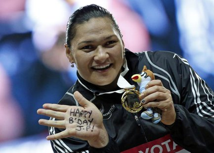 Winner Valerie Adams of New Zealand shows her gold medal at the victory ceremony for the women's shot put final during the IAAF World Athlet