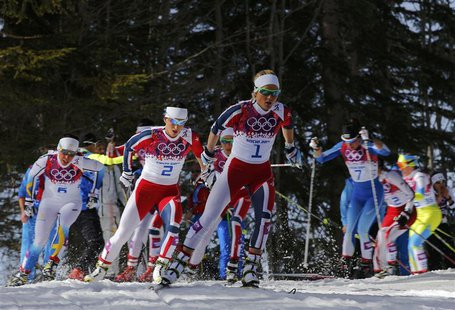 Norway's Therese Johaug (C) and Marit Bjoergen (centre L) ski ahead of the pack during the women's cross-country 30 km mass start free event