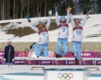 Winner Norway's Marit Bjoergen (C) celebrates next to her compatriots, second placed Therese Johaug (L) and third placed Kristin Stoermer St
