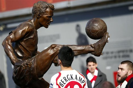 Arsenal fans look at a statue of former striker Dennis Bergkamp after it was unveiled before their English Premier League soccer match again