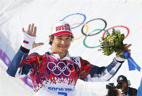 Russia's winner Vic Wild celebrates during flower ceremony after the men's parallel snowboard finals at the 2014 Sochi Winter Olympic Games