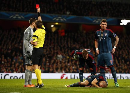 Arsenal's goalkeeper Wojciech Szczesny (L) receives a red card from referee Nicola Rizzoli after a foul against Bayern Munich's Arjen Robben