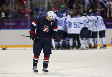 Team USA's Zach Parise skates away as Finland celebrates their win in their men's ice hockey bronze medal game at the Sochi 2014 Winter Olym