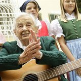 Maria von Trapp, daughter of Austrian Baron Georg von Trapp, prepares to play a guitar and sing with traditionally dressed children in front