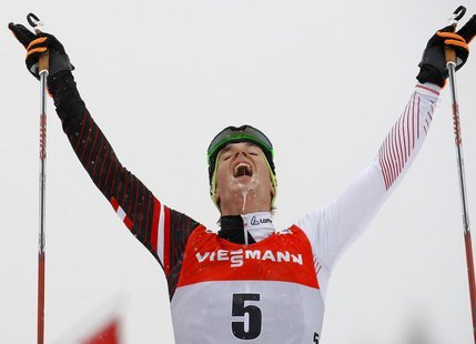 Johannes Duerr of Austria celebrates as he crosses the finish line to third place during the men's FIS World Cup cross-country skiing 9km fr