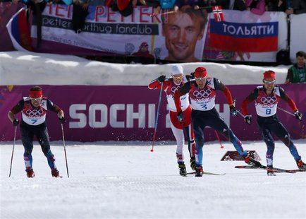 Russia's Alexander Legkov (2nd R) Maxim Vylegzhanin (L) and Ilia Chernousov (R) race to the finish line to take first, second and third plac