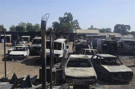 A man walks between vehicles that were destroyed during an attack by Boko Haram militants in Bama, Borno State, February 20, 2014. REUTERS/S