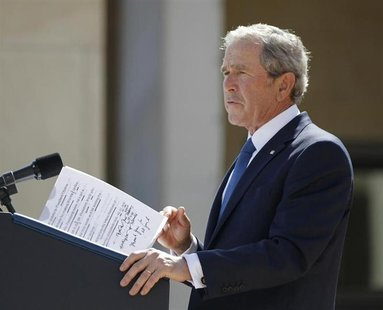 Former U.S. President George W. Bush delivers remarks with some hand-written notes during the dedication ceremony of the George W. Bush Pres