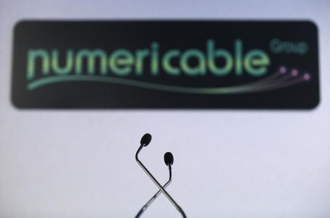 A logo of French cable operator Numericable is seen behind microphones during a news conference in Paris, October 28, 2013. REUTERS/Christia