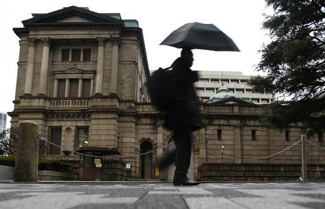 A pedestrian holding an umbrella to take shelter from rain and hail walks past the Bank of Japan headquarters building in Tokyo December 20,