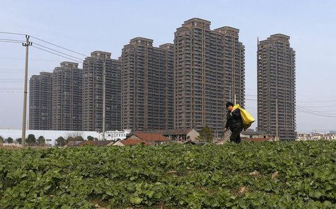 A farmer walks past a vegetable field near newly-built residential buildings in Jiaxing, Zhejiang province February 23, 2014. REUTERS/Willia
