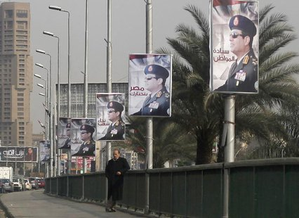 A man stands on a bridge where huge posters of Egypt's Army chief Field Marshal Abdel Fattah al-Sisi are hanged in central Cairo February 3,
