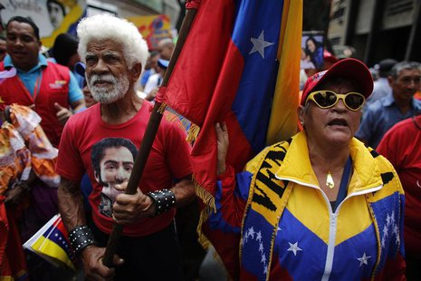 An elderly protester carries a Venezuela's flag during a march for peace in downtown Caracas February 23, 2014. REUTERS/Tomas Bravo