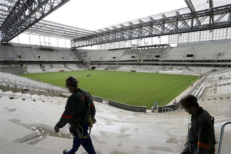 Workers walk inside the Arena da Baixada soccer stadium as it is being built to host matches of the 2014 World Cup in Curitiba, February 17,