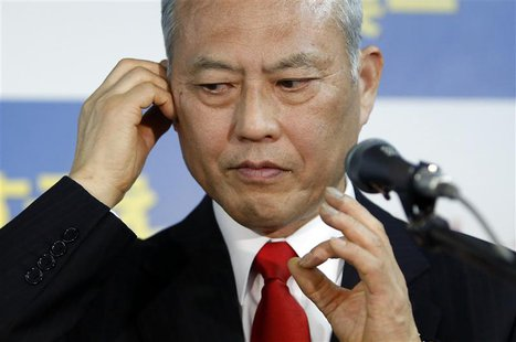 Japan's former health minister Yoichi Masuzoe checks his earphone as he prepares for an interview at his office in Tokyo February 9, 2014. R
