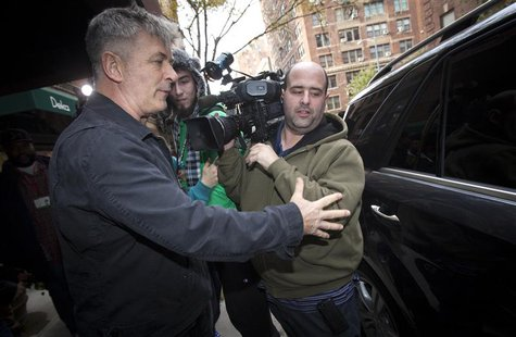 Actor Alec Baldwin directs a TV photographer out of his way in front of his apartment building in New York November 15, 2013. REUTERS/Carlo