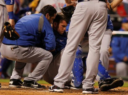 New York Mets catcher Josh Thole is helped to his feet after a collision at home plate with the Philadelphia Phillies Ty Wigginton (unseen)