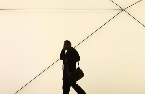 A man talks by a mobile phone as he walks past the Samsung stand at the Mobile World Congress in Barcelona February 24, 2014. REUTERS/Albert