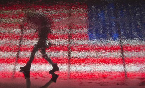 A woman is reflected in the wet pavement as she walks past a U.S. flag billboard in Times Square during a rare winter thunderstorm in New Yo