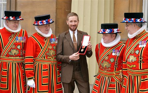 British cyclist Bradley Wiggins poses for a photograph with his Knighthood medal, and Yeomen of the Guard, awarded to him by Queen Elizabeth